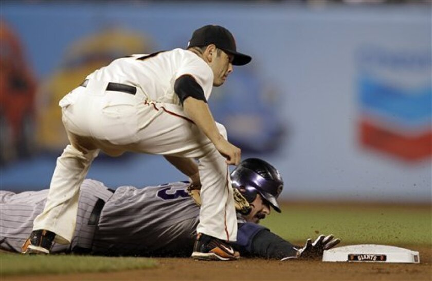 Colorado Rockies' Jason Giambi, bottom, is tagged out by San Francisco Giants second baseman Freddy Sanchez as he is caught in a rundown on a ground ball by Ryan Spilborghs during the fourth inning of a baseball game in San Francisco, Tuesday, Aug. 31, 2010. (AP Photo/Marcio Jose Sanchez)