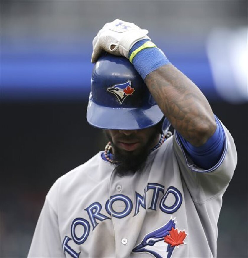 Toronto Blue Jays' Jose Reyes holds his helmet after he popped out on a bunt to Detroit Tigers pitcher Drew Smyly in the eighth inning of a baseball game in Detroit, Tuesday April 9, 2013. (AP Photo/Paul Sancya)