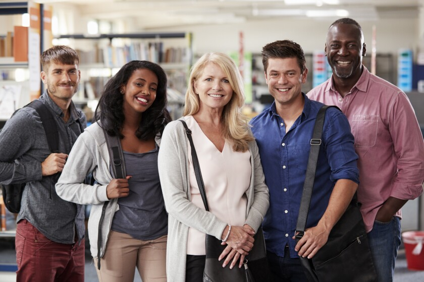 Portrait Of Mature Student Group Standing In Library