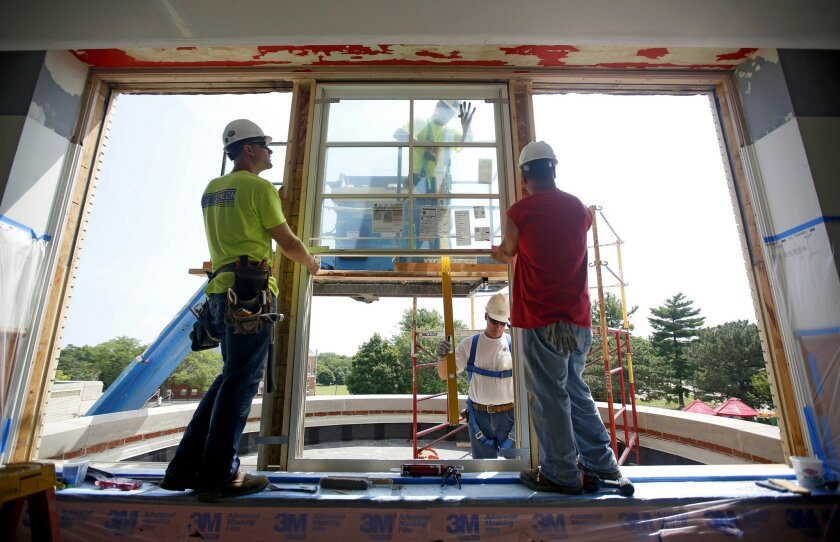 Construction workers install windows in a new school site. Vista Unified School District is deliberating whether to adopt a project labor agreement for construction under its $247 school bond program.