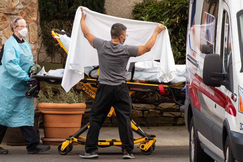 Workers transport a patient in Kirkland, Wash.