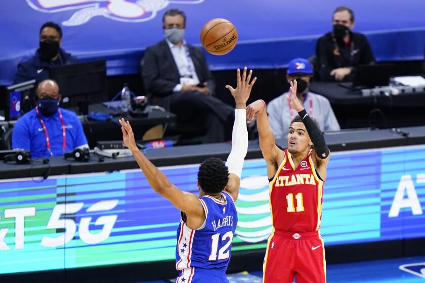 Trae Young, de los Hawks de Atlanta, dispara sobre la defensiva de Tobias Harris, de los 76ers de Filadelfia, en la segunda mitad del quinto juego de la semifinal de la Conferencia Este, el miércoles 16 de junio de 2021, en Filadelfia. (AP Foto/Matt Slocum)