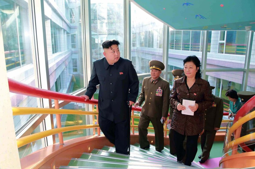 This undated picture released from North Korea's official Korean Central News Agency on Oct. 26 shows North Korean leader Kim Jong Un, left, visiting a home for infants and orphans in Pyongyang.