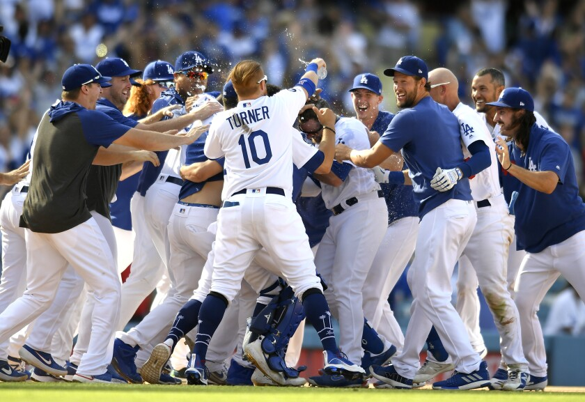 The Dodgers celebrate after Max Muncy's double ends an 11-10 victory over the Padres on Sunday at Dodger Stadium.