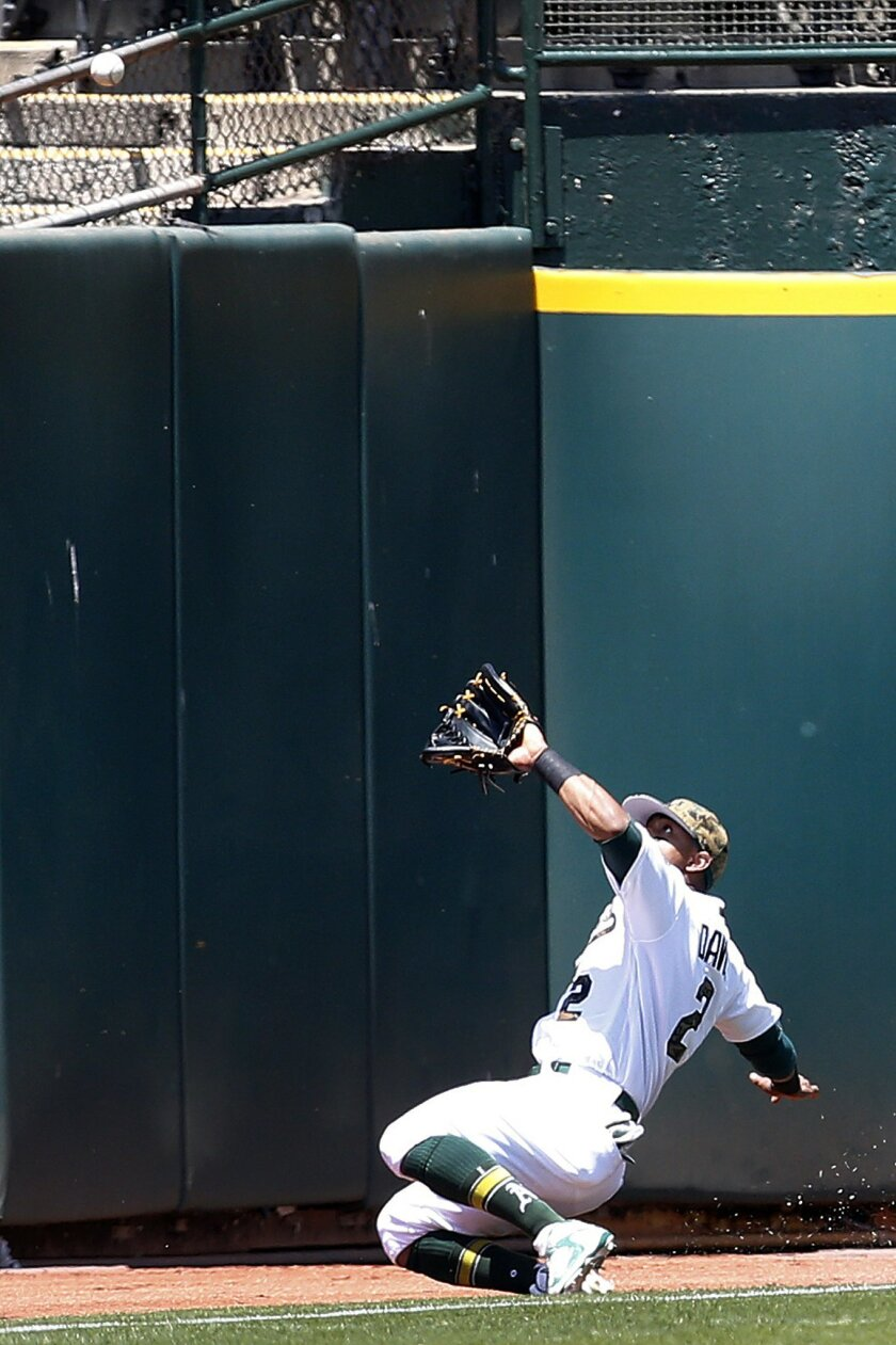 Oakland Athletics left fielder Khris Davis makes a sliding catch against the Minnesota Twins in the first inning of a baseball game Monday, May 30, 2016, in Oakland, Calif. (AP Photo/Tony Avelar)