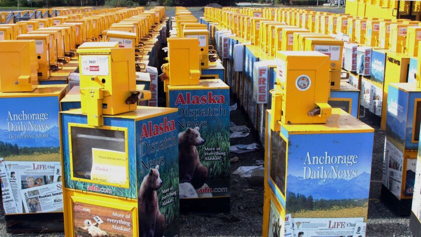 Hundreds of old newspaper sales boxes are shown Monday in a vacant lot near the former offices of the Alaska Dispatch News in Anchorage.
