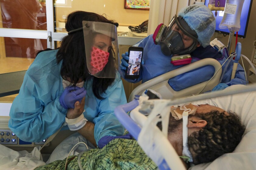 A woman holds the hand of a patient in a bed while another person holds up a phone.
