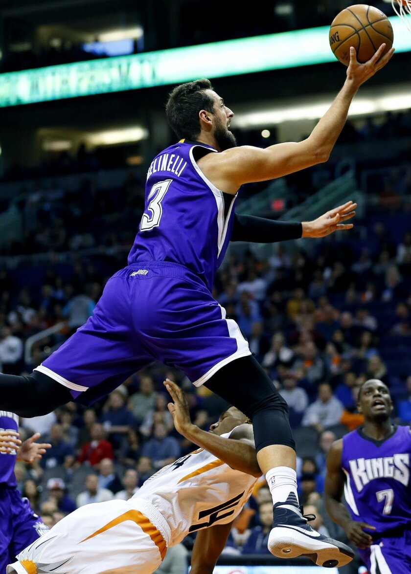 Sacramento Kings' Marco Belinelli, of Italy, is fouled by Phoenix Suns' Ronnie Price during the first half of an NBA basketball game, Wednesday, Nov. 4, 2015, in Phoenix. (AP Photo/Matt York)