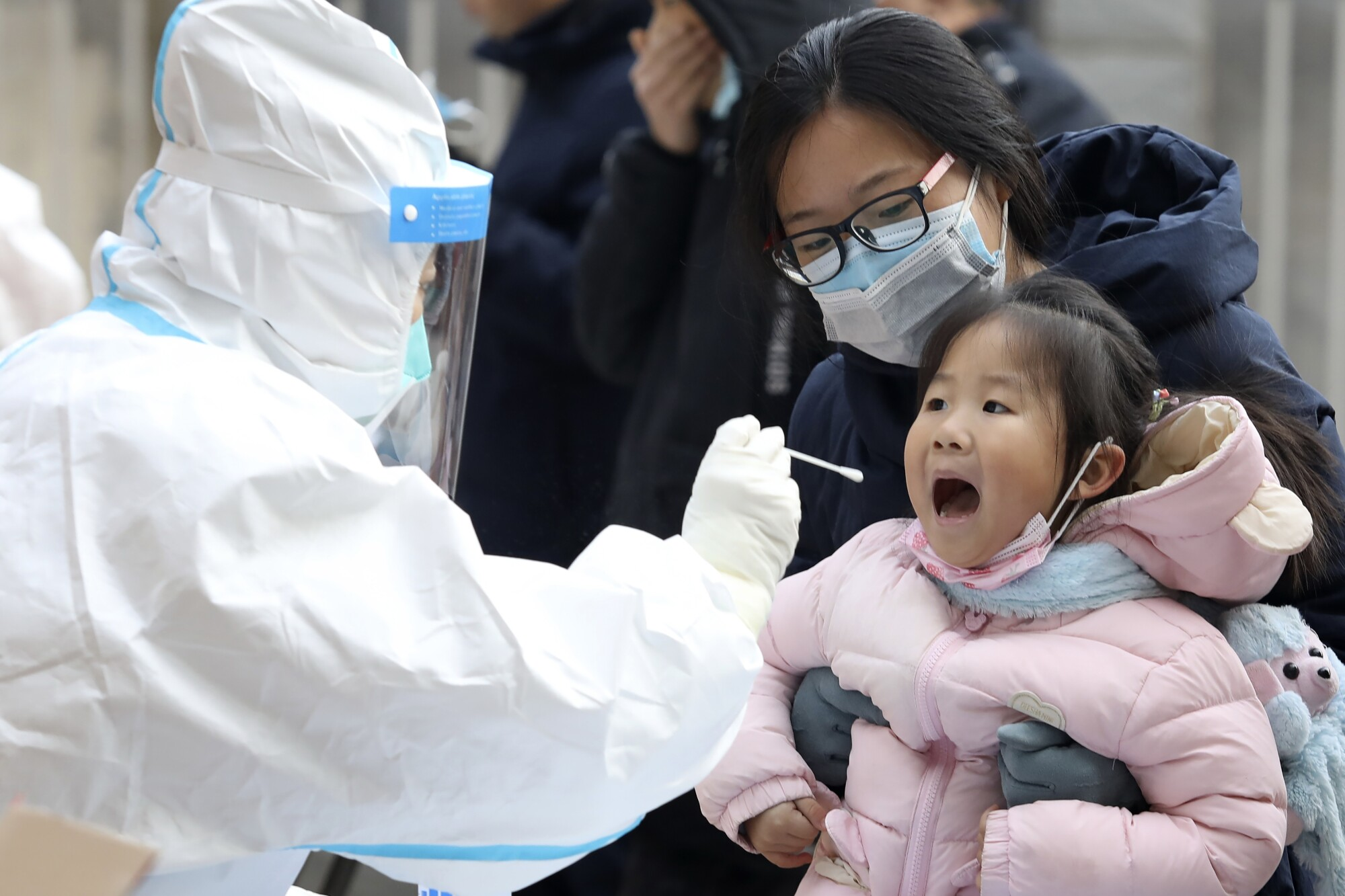 A worker in a protective suit takes a swab from a child for a coronavirus test in Shijiazhuang, in northern China.