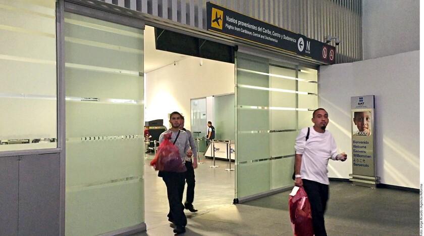 """Un grupo de connacionales repatriados recibió en el AICM los objetos que portaban el día de su detención en EU y un """"kit del migrante"""", que incluye alimentos y un boleto de autobús."""