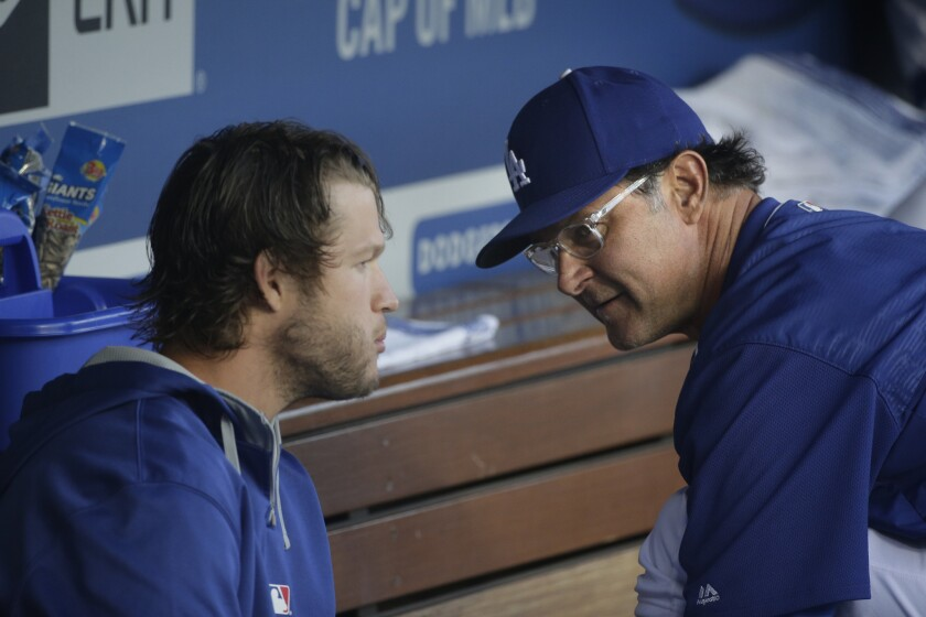 Dodgers Manager Don Mattingly, right, talks to pitcher Clayton Kershaw before Friday's game. Kershaw was scratched from his start, but is expected to pitch Saturday.