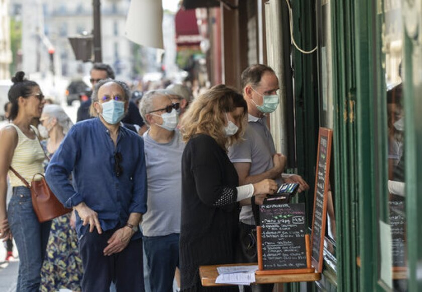 People wear masks to help curb the spread of the coronavirus line up to buy an ice-cream in Paris, Thursday May 21, 2020 as France gradually lifts its Covid-19 lockdown. (AP Photo/Michel Euler)