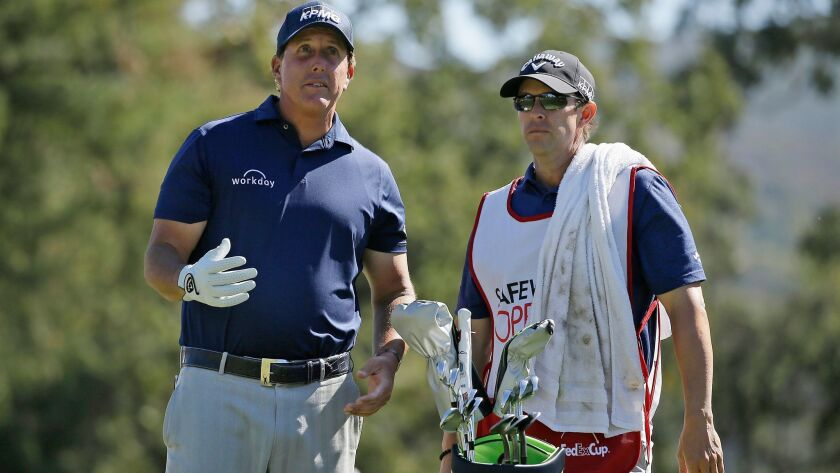 Phil Mickelson, left, reads the wind while standing with his caddie, Tim Mickelson, right, on the second tee of the Silverado Resort North Course during the final round of the Safeway Open PGA golf tournament last year in Napa, Calif.