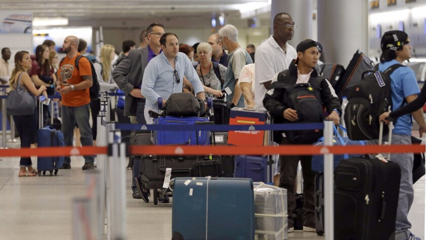 Travelers wait in line to check luggage at Miami International Airport. The FAA has fined Alaska, American, United and Southwest Airlines for giving inaccurate compensation information to passengers who were bumped off a flight or lost luggage.