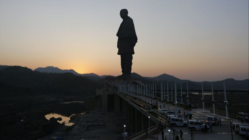 The Statue of Unity is silhouetted against the setting sun at Kevadiya Colony in Narmada district of