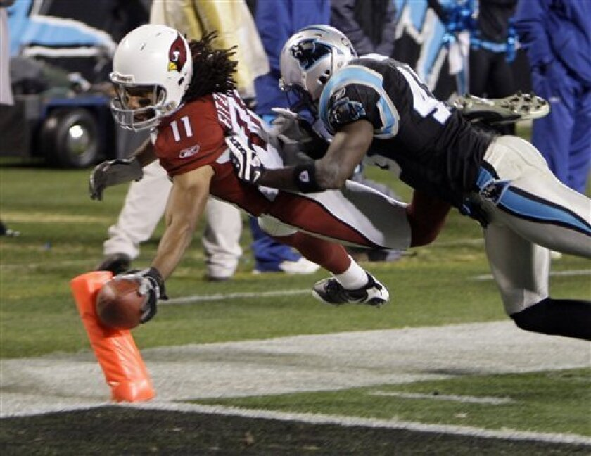 Arizona Cardinals' Larry Fitzgerald (11) reaches the ball over the goal line for a touchdown as Carolina Panthers' Chris Harris (43) defends during the second quarter of an NFL divisional playoff football game in Charlotte, N.C., Saturday, Jan. 10, 2009. (AP Photo/Chuck Burton)
