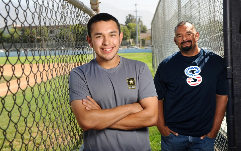 Sylmar High School baseball player Mario Cruz and head coach Ray Rivera stand in the dugout. Cruz along with two other players joined the army and will be leaving for boot camp soon.