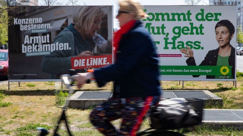 In a file photo from April 2019, a bicyclist in Berlin passes election campaign posters for the Left (die Linke) party and the Greens party (poster at right) during campaigning for the recent European Parliament elections.