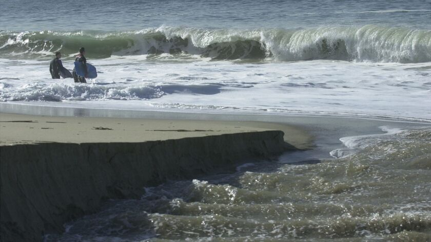 CPT.URBAN–RUNOFF–1.010706.MCD Two bodyboarders walk out into the surf where Aliso Creek empties into