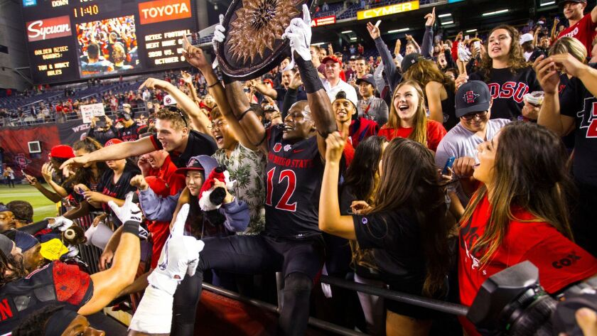 SDSU safety Malik Smith holds up the Aztec Warrior's shield as he joins SDSU fans in the stands to cheer.