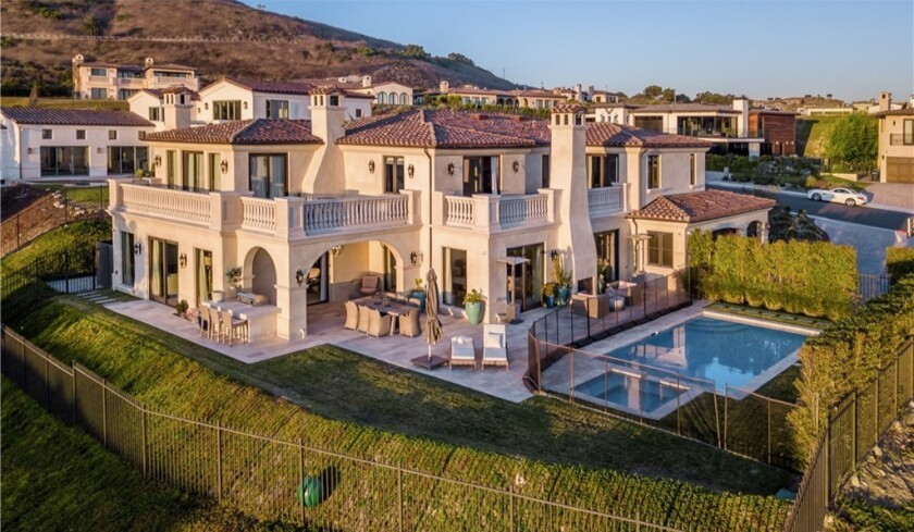 The two-story villa takes in sweeping ocean and golf course views from multiple balconies and an entertainer's backyard.