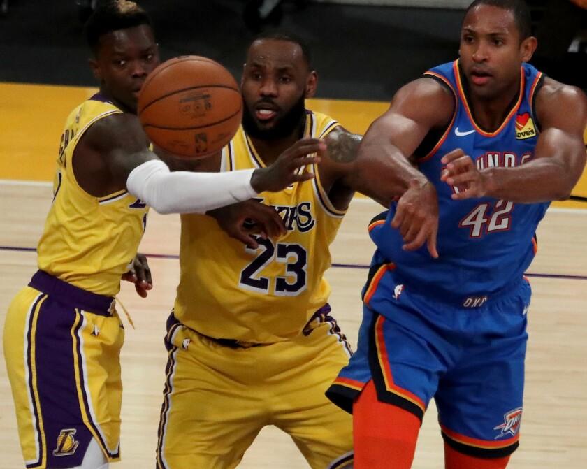 Lakers defenders Dennis Schroder, left, and LeBron James pressure Thunder big man Al Horford in overtime.