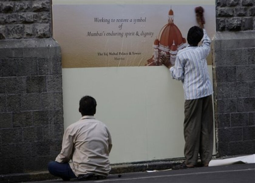 Workers put-up posters on wooden boards outside the Taj Mahal hotel in Mumbai, India, Tuesday, Dec. 2, 2008. (AP Photo/Gautam Singh)
