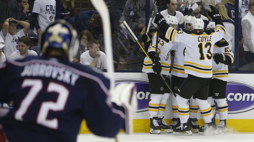 Boston Bruins players celebrate their goal against the Columbus Blue Jackets during the third period