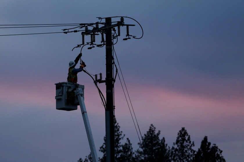 A Pacific Gas & Electric lineman works to repair a power line on Nov. 26, 2018, in Paradise, Calif. PG&E may shut off power to some counties in Northern California in advance of critical fire weather.