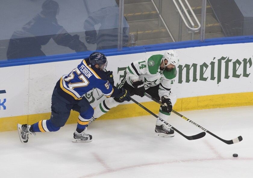 St. Louis Blues' David Perron (57) and Dallas Stars' Jamie Benn (14) battle for the puck during the second period of NHL qualifying round game in Edmonton, Alberta, on Sunday, Aug. 9, 2020. (Jason Franson/The Canadian Press via AP)