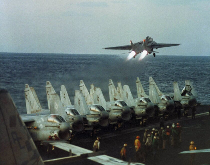 A U.S. Navy F-14 lifts off over arrow of A7 Corsairs on the deck of the aircraft carrier USS John F. Kennedy in the Red Sea late, Jan. 25, 1991 on a mission to attack an Iraqi position. Allied forces have flown more than 8,000 missions in the first five days of Operation Desert Storm, and carrier-b