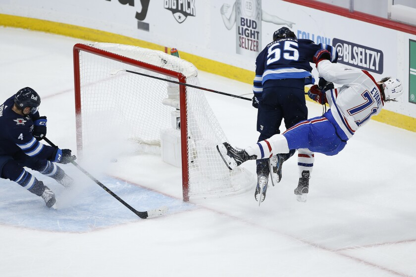 Winnipeg Jets' Mark Scheifele (55) hits Montreal Canadiens' Jake Evans (71) after Evans scored an empty-net goal during the third period of Game 1 of an NHL hockey Stanley Cup second-round playoff series Wednesday, June 2, 2021, in Winnipeg, Manitoba. (John Woods/The Canadian Press via AP)