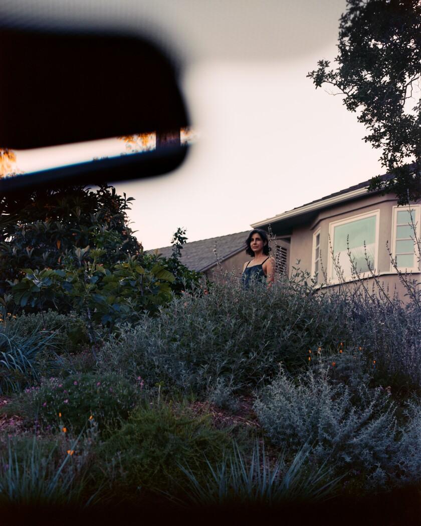 La curadora Meldia Yeseyan se encuentra en una colina cubierta de plantas con una casa en la distancia.