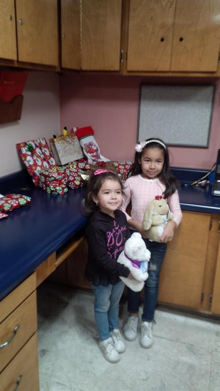 Fotografía cedida por Randy Heiss donde aparece la niña Dayami (d), de 8 años, junto a su hermana Ximena (i), 4, sosteniendo en la cocina de su casa en México los regalos que les trajo de Estados Unidos Randy Heiss y su esposa después de encontrar su lista de deseos de Navidad. EFE/Cortesía Randy Heiss/SOLO USO EDITORIAL/NO VENTAS