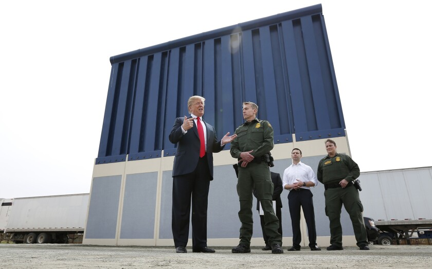 President Trump with Border Patrol officials in front of a piece of a tall border wall prototype