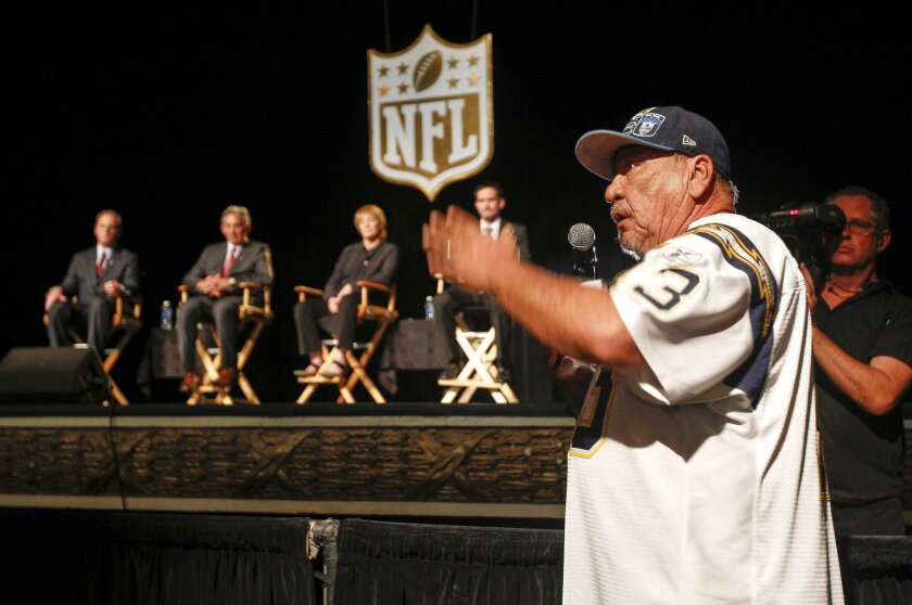 Chargers fan Jesse Constancio, a season ticket holder for 22 years, turns to the crowd as he takes his turn to speak to NFL representatives sitting on stage at a town hall meeting on the Chargers at Spreckles Theatre in San Diego.