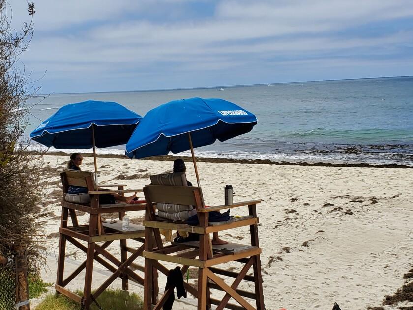 Lifeguards watch over a largely empty Marine Street Beach in La Jolla last week.