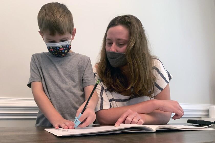 Emily Goss acompaña a su hijo de 5 años a hacer la tarea en la cocina de su casa en Monroe, Carolina del Norte, el lunes 13 de septiembre de 2021. (Foto AP/Sarah Blake Morgan)