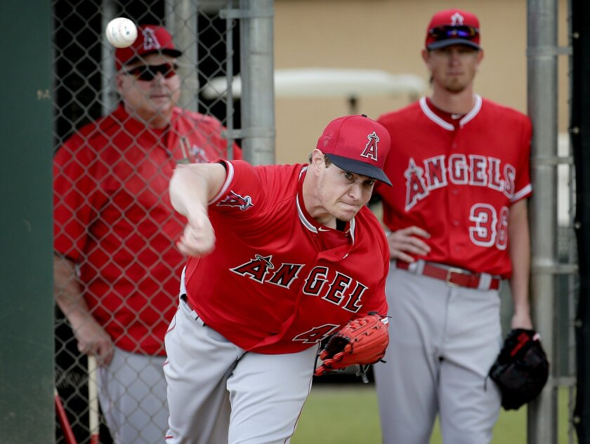 Los Angeles Angels' Garrett Richards throws as manager Mike Scioscia, left, and teammate Jered Waver look on during spring training baseball workouts, Friday, Feb. 19, 2016, in Tempe, Ariz. (AP Photo/Matt York)