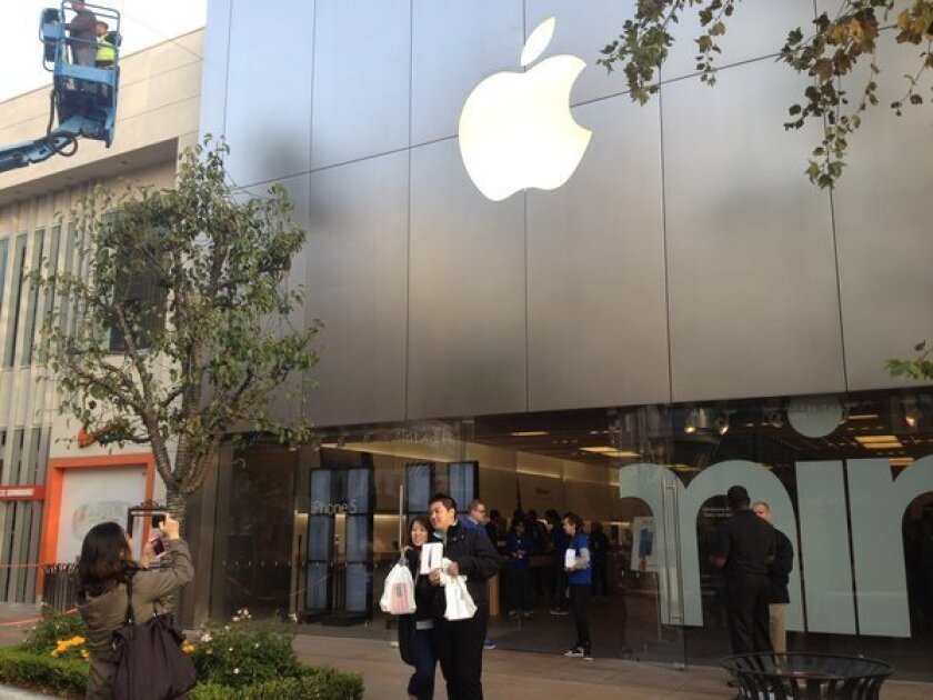Taiwanese tourists with their new iPad minis pose for launch-day photos at the Apple store in L.A.'s Fairfax district.