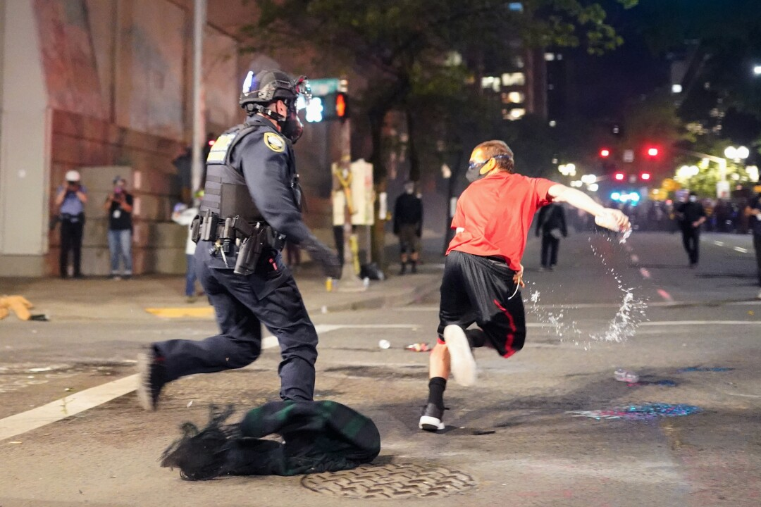 A protester escapes a federal officer during an arrest attempt in Portland, Ore.
