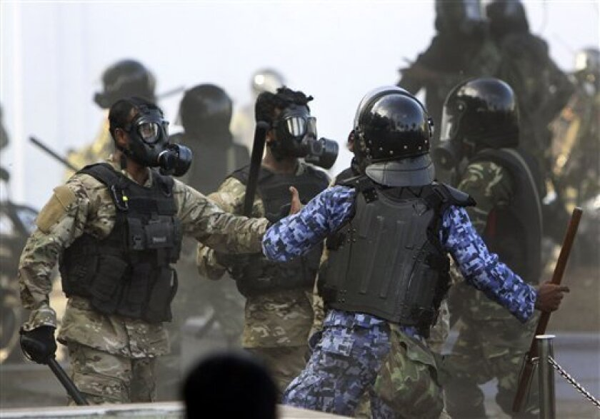 A Maldives police officer, in blue, charges soldiers during a clash in Male, Maldives, Tuesday, Feb. 7, 2012. Maldives President Mohamed Nasheed presented his resignation in a nationally televised address Tuesday afternoon after police joined the protesters and then clashed with soldiers in the streets. (AP Photo/Sinan Hussain)