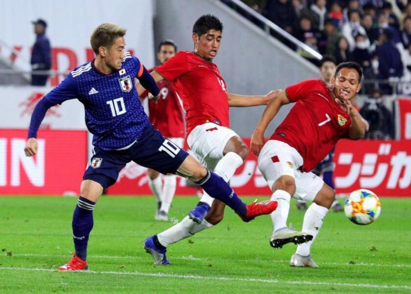 El centrocampista japonés Shinji Kagawa (izq) lucha por el balón con el centro boliviano Leonel Justiniano (dcha) durante el partido amistoso disputado este martes en Kobe (Japón).EFE