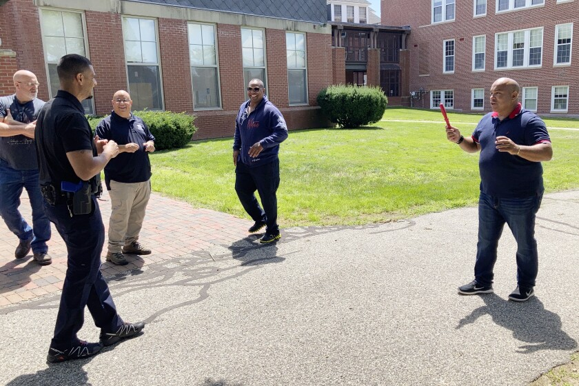 In this July 28, 2021 photo, Jose Otero from the New York City Police Department, right, holds a plastic knife after completion of a role-playing scenario in which New England police officers were learning de-escalation techniques from the Police Executive Research Forum in Saco, Maine. (AP Photo/David Sharp)