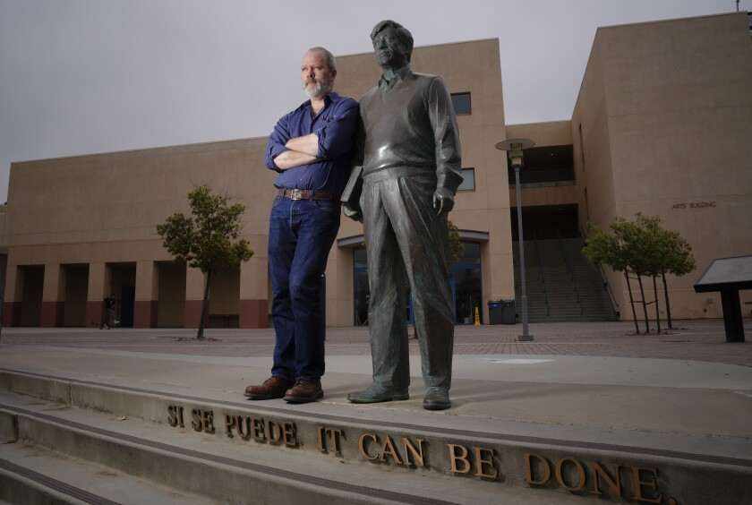 James Nelson, 50, poses with the statue of civil rights leader Cesar Chavez, which he and his late wife and fellow sculptor, T.J. Dixon, designed and installed at Cal State San Marcos in 1997.