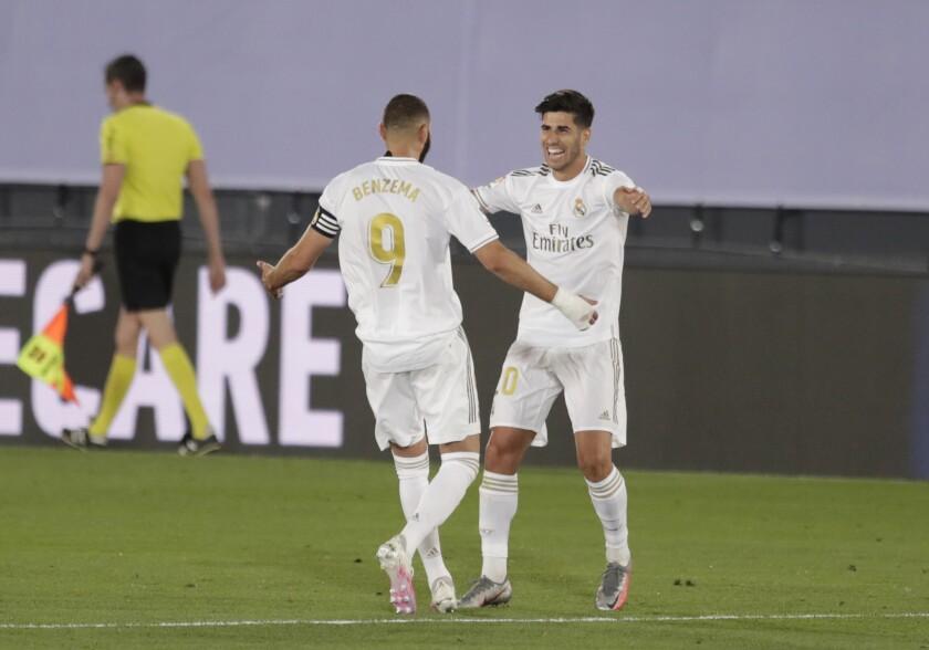 Marco Asensio, del Real Madrid, festeja con su compañero Karim Benzema después de anotar en un partido de La Liga.