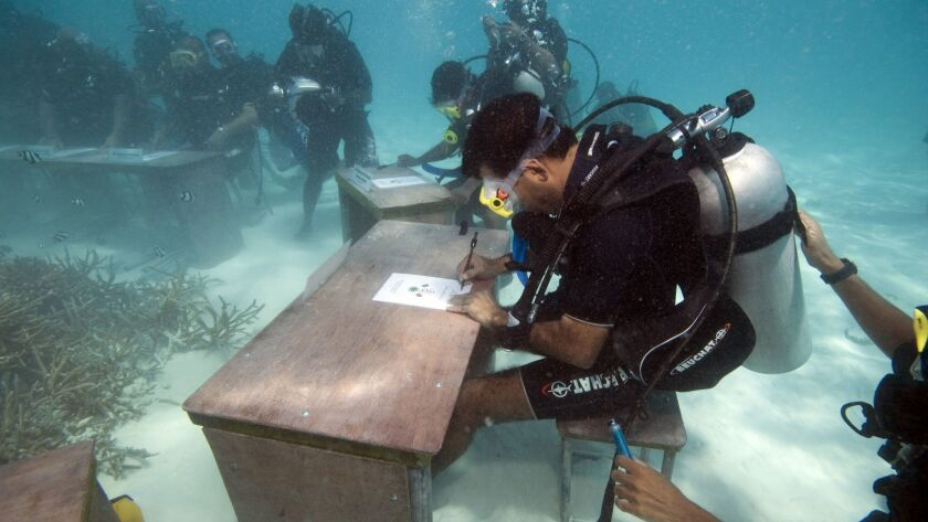 Maldivian President Mohammed Nasheed signs a document calling on all countries to cut down their car