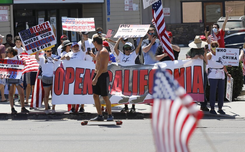 A skateboarder films protesters Sunday along Mission Boulevard in Pacific Beach during a rally demanding the reopening of California.