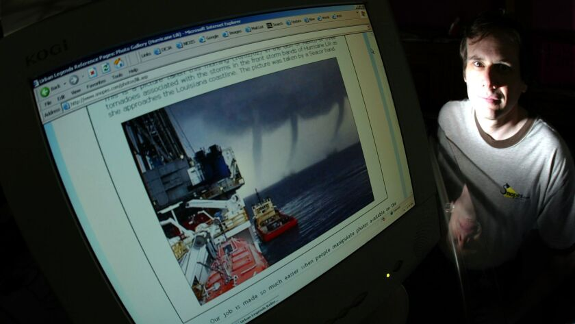 David Mikkelson next to his computer monitor with a doctored storm photo in which two tornadoes were added to the original photo, which had only one.