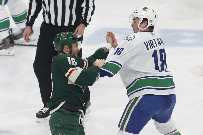 Minnesota Wild's Jason Zucker, left, and Vancouver Canucks' Jake Virtanen fight during the first period of an NHL hockey game Thursday, Feb. 6, 2020, in St. Paul, Minn. Both received fighting penalties. (AP Photo/Jim Mone)